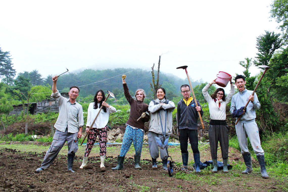 volunteers-excited-holding-farming-equipment-workaway-travel-adventure