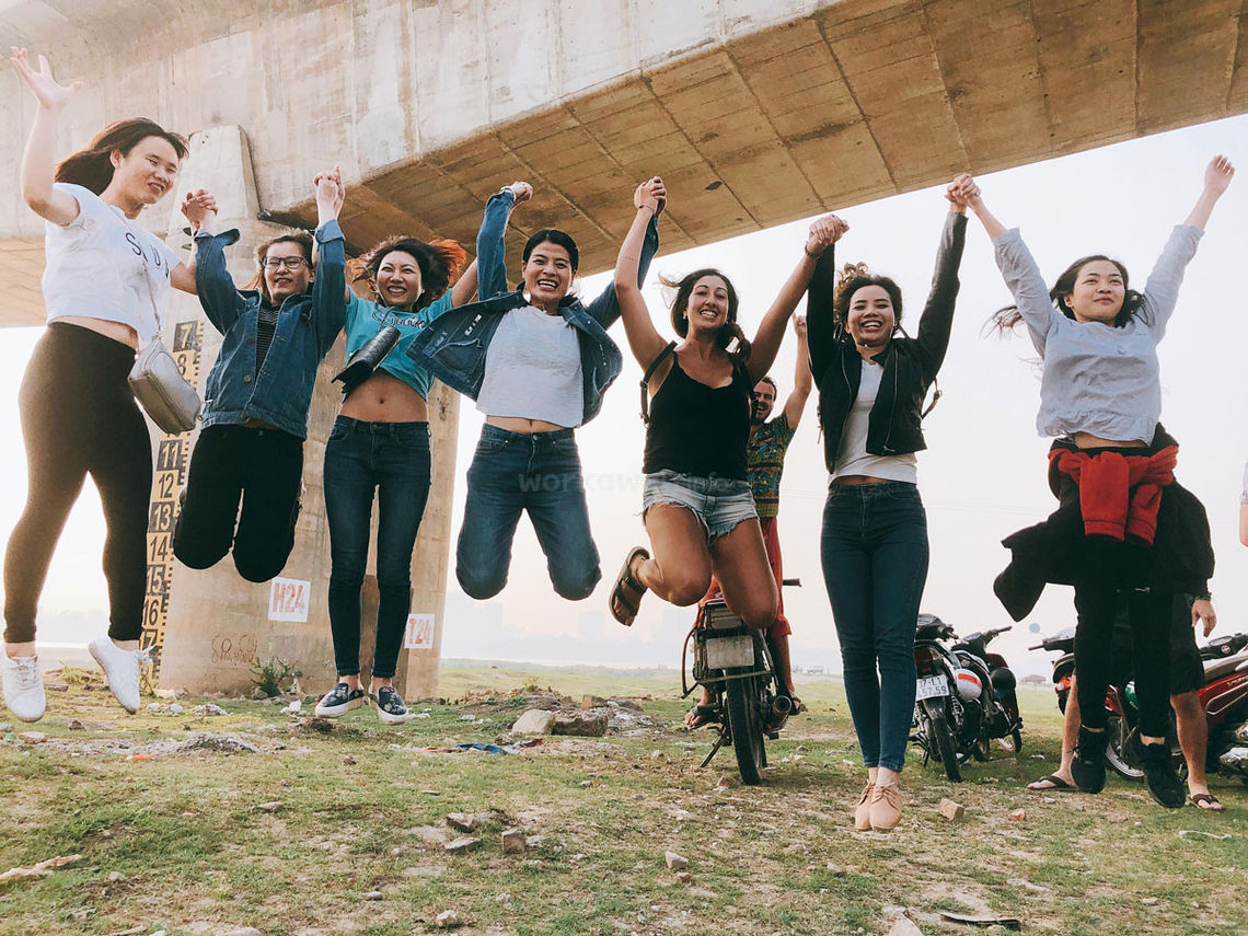 group-of-female-travellers-jumping-for-joy