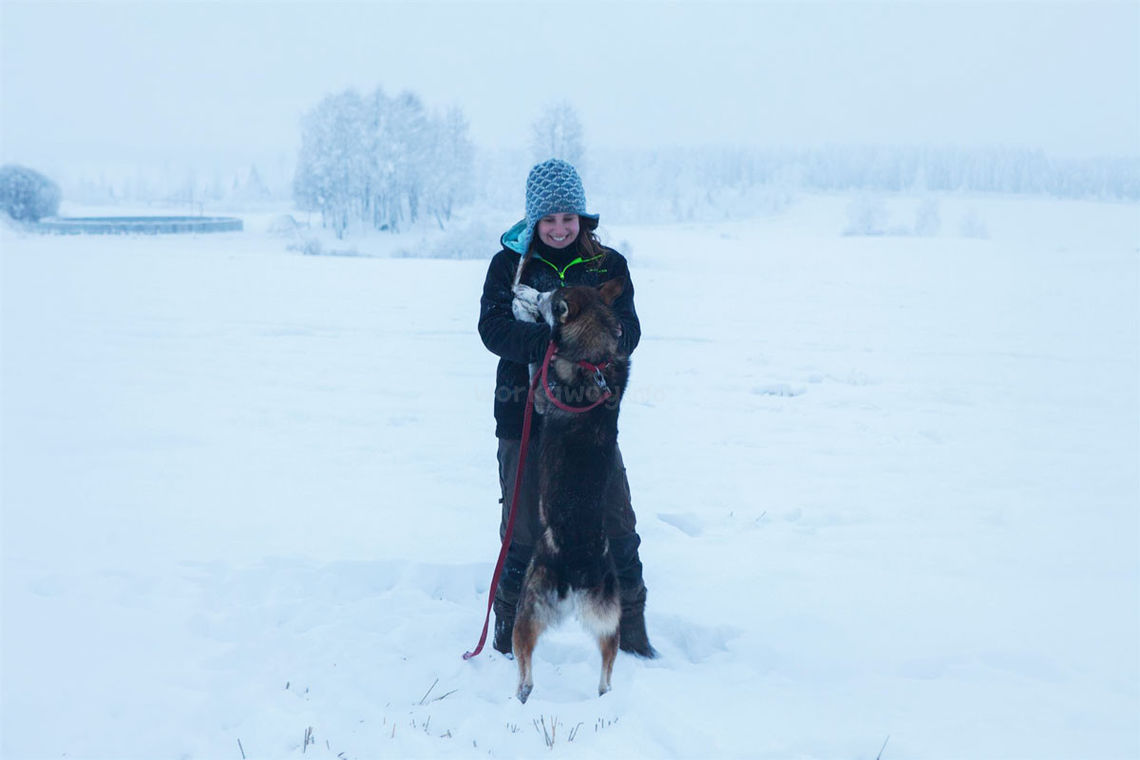 smiling solo female traveller with husky in the snow