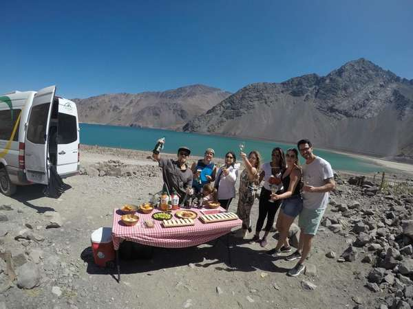 group al fresco meal with caravan and lake background