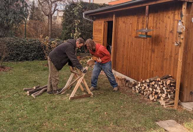 workaway host and traveller chopping wood together