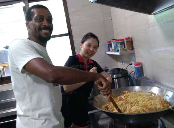 Kenneth and workawayer cooking in kitchen together smiling