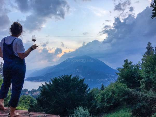 solo traveller enjoy rooftop view mountains with wine