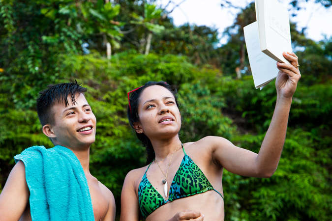 two travellers read book in tropical beach