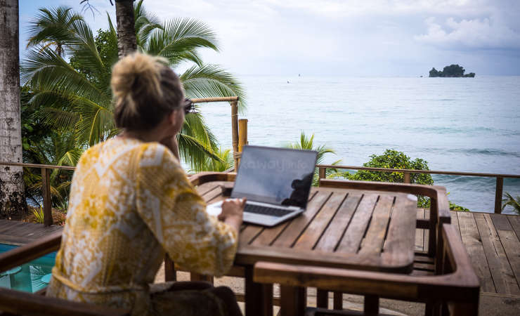 digital nomad on laptop admiring ocean view outdoors