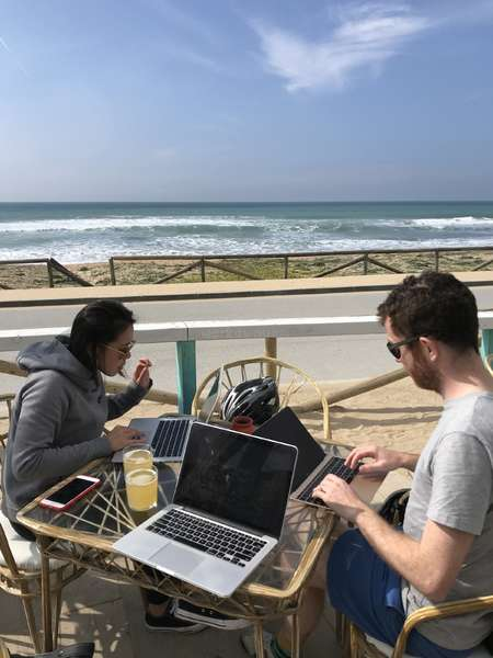 digital nomad friend group working ourdoors ocean view