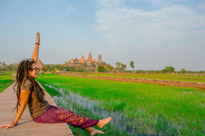female solo traveller admire Thailand field temple backdrop