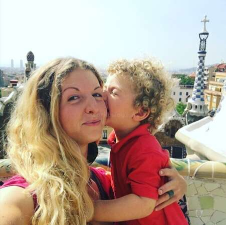 little boy Adam kissing workawayer fenia on cheek with balcony scenery background