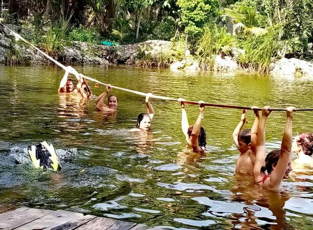 group sustainable adventure river dip fun volunteers hold on to rope nature outdoor activity