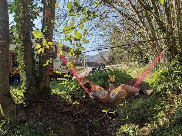 van life slow travel workaway reading break on hammock in nature forest trees