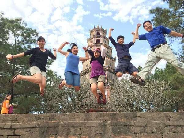 su family with children jumping up with pagoda background travel